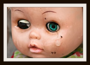 Concept: Abandoned Person. Close up of an old doll`s face with tear