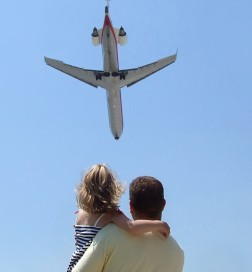 Father and Daughter Looking at Airplane